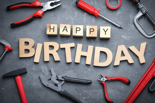 Tools and words HAPPY BIRTHDAY on grey stone background, flat lay