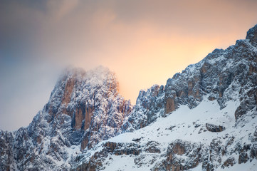 Mountain peaks with clouds at sunrise. Snow-covered winter Dolomite Alps. Val Di Fassa, Italy. Beautiful winter landscape