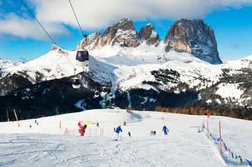 Ski slopes on ski resort in winter Dolomite Alps. Val Di Fassa, Italy. Skiers going down the slope. Winter holidays, travel destination