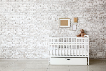 Stylish baby bed near brick wall in interior of children's room
