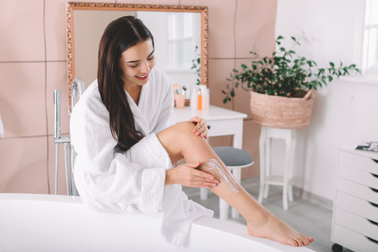 Beautiful young woman applying cream on her legs in bathroom