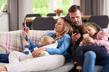 Parents and children using mobile phone in living room