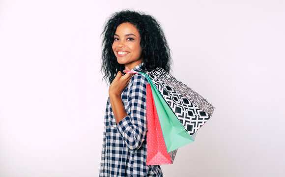 Shop till you drop. Smiling African American woman in plaid shirt is posing in profile, looking at the camera and holding three shopping bags in her left hand.