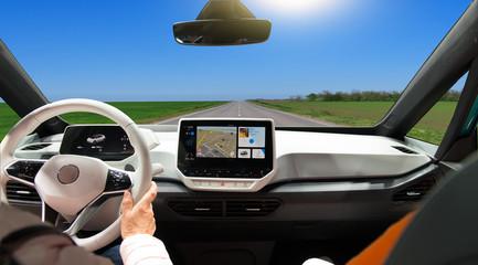Two women driving a super modern car on an asphalt highway