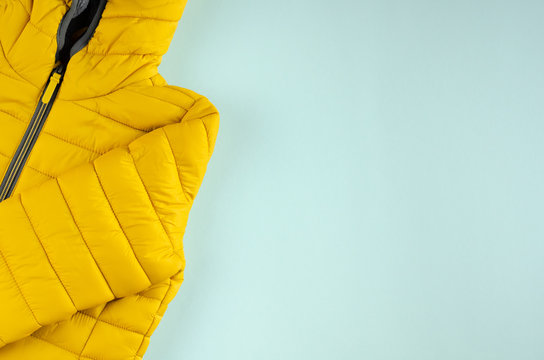 Yellow kids winter jacket composition on blue background.
