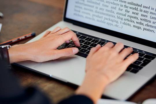 Crop office worker typing text on laptop