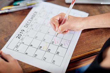 Girl writing reminders on calendar page for December 2019