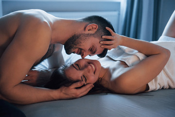 Natural daylight. Sexy couple lying on the bed and enjoying themselves at morning time