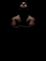 Brown man with hairy chest and arms folded looking up towards the light in low key lighting