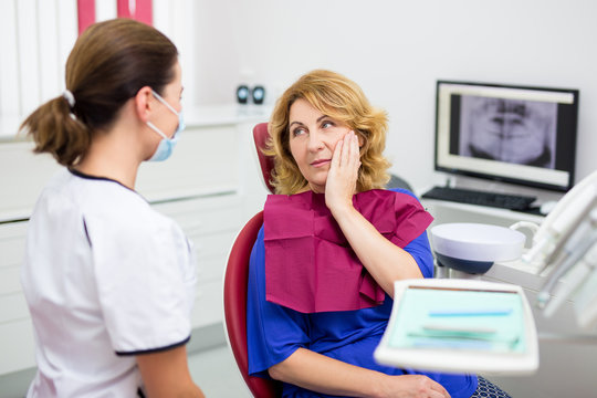 attractive mature woman with pain in dentist office with doctor