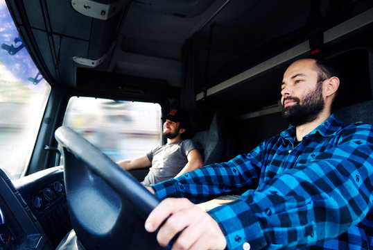 Two young men driving a truck.