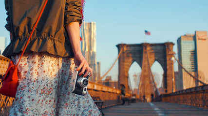 Young photographer with a retro camera on the Brooklyn Bridge