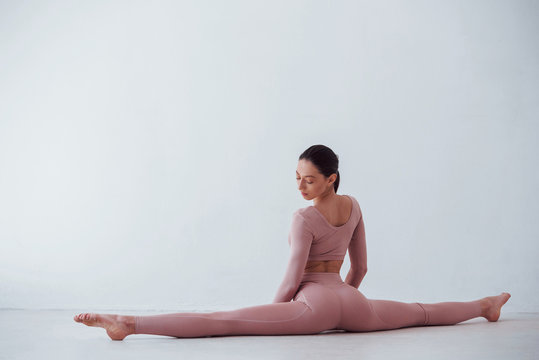 Doing the splits. Caucasian pretty woman doing exercises against white background in the studio