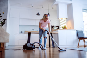 Smiling cheerful caucasian blonde housewife using vacuum cleaner to clean floor in living room. Home interior.