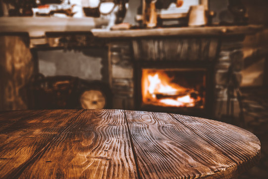 Table top with blurred fireplace and cosy home interior background.
