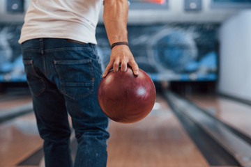 This is gonna be the strike. Rear particle view of man in casual clothes playing bowling in the club