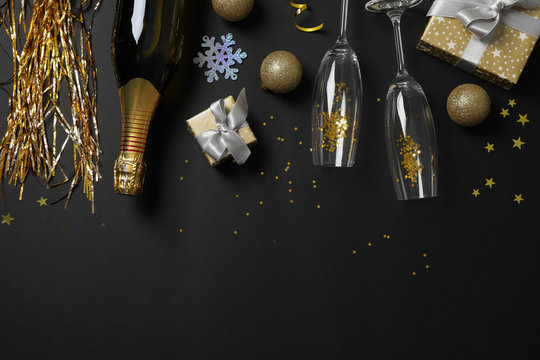 Champagne bottle, glasses and christmas baubles on black background, copy space