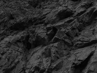 Black stone background. Mountain close-up. Fragment of the mountain.   Black rock texture.