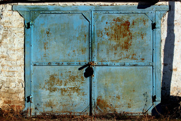 Old metal garage doors. Flaking paint and rust on gates of abandoned building.
