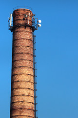 Old brick pipe with antennas against blue sky background