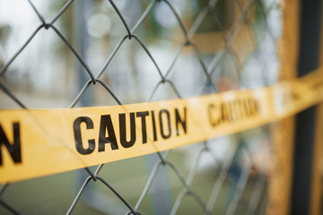 Do not enter. Yellow caution tape on the metal fence at daytime. Crime scene