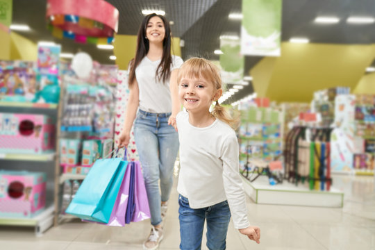 Girl keeping hand of mom and running forwardn in toy store