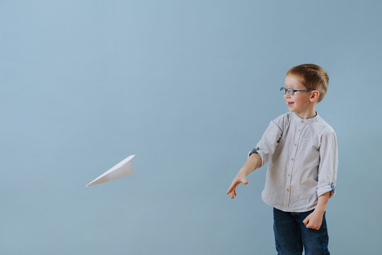 Cute little ginger boy launched a paper plane to fly over blue background