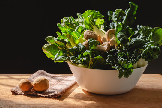 Green leafy vegetables and mushrooms in white bowl on wood table and black background by the window with morning sun light,Should eat daily for good health, Is a diet that has many vitamins and fiber.