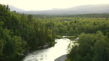 Fototapete - The sun setting over a river in a  green, mountain wilderness. Jamtland, Sweden.