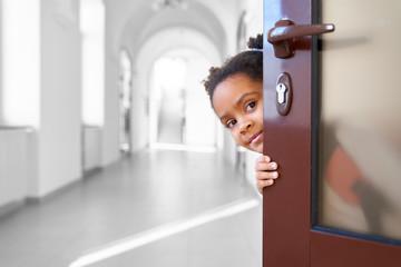 Pretty African girl hiding from opened door in school.