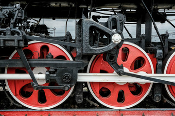 Red wheels of an old Russian locomotive on the rails close-up.