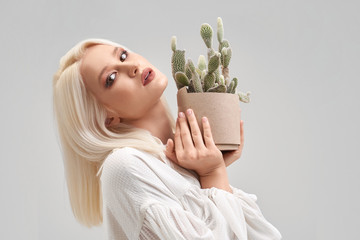 Beautiful blonde girl with make up holding pot with cactus