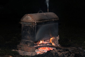 cooking smoked meats in a mobile metal smokehouse at the stake