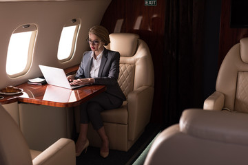 confident businesswoman working on laptop in plane during business trip