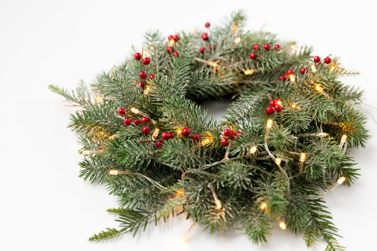 winter holidays, new year and decorations concept - wreath of fir branches with red berries and garland lights on white background