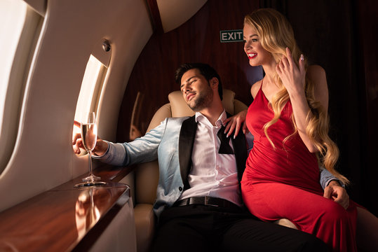 beautiful elegant couple with champagne sitting in airplane