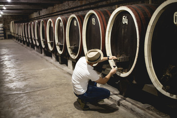 Winemaker working in oak barrels at cellar stock photo