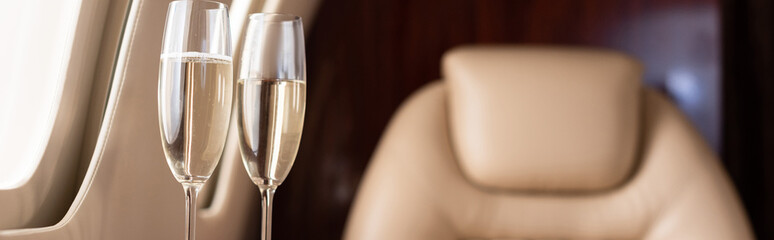 panoramic shot of champagne glasses in private jet