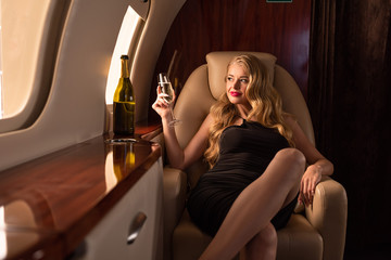 attractive sexy woman with champagne sitting in plane