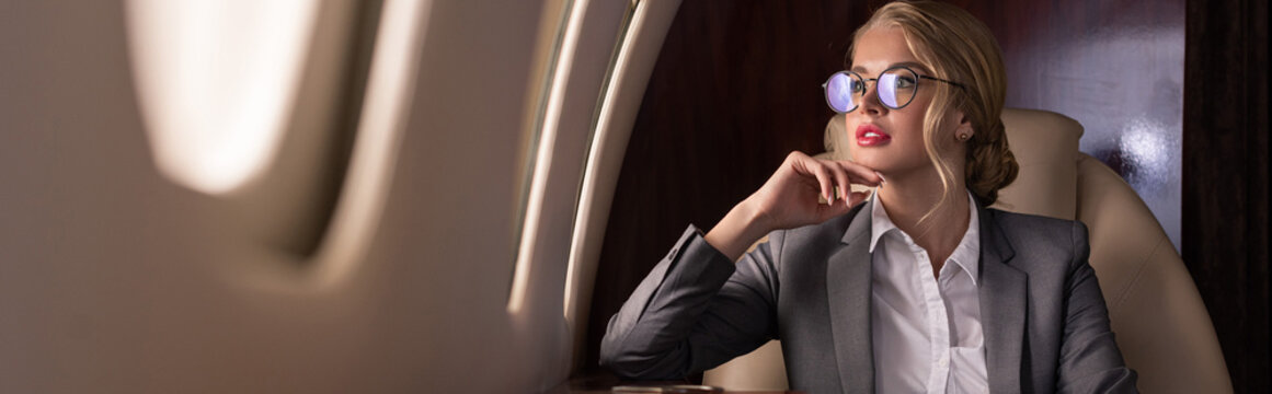 attractive business leader sitting in plane during business trip