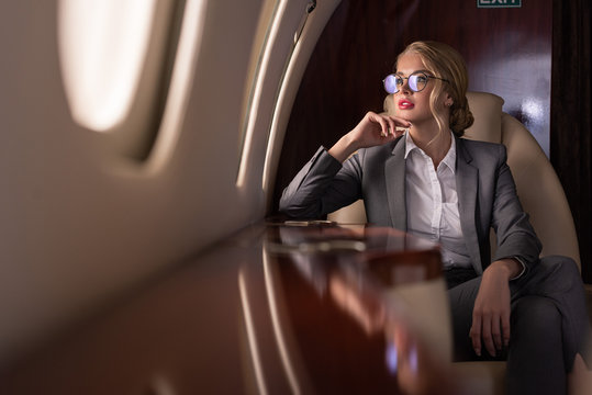 Professional businesswoman in glasses sitting in plane during business trip