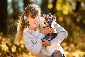 girl sits and relax on the ground in the autumn forest and plays with Yorkshire Terrier small dog