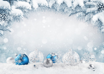 Merry Christmas card. Blue christmas balls and baubles on the snow with fir branches.