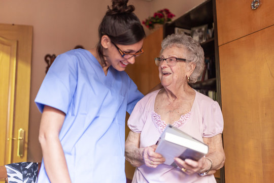 Happy Senior woman with her caregiver at home holding a book and smiling. Senior home care concept.