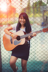 asian teenager playing spanish guitar with happiness emotion