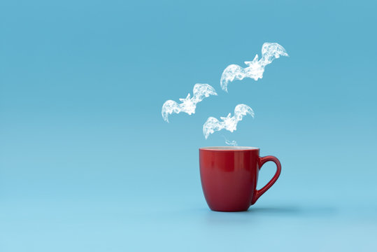 Steam in three bats shape flying from coffee cup against blue background. Morning drink. Halloween celebration concept. Copy space