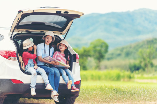 Group asian family children checking map and pointing on the car adventure and tourism for destination and leisure trips travel for education and relax in nature park .  Travel vacations