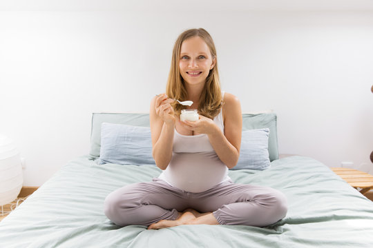 Cheerful expectant mother keeping healthy diet. Pregnant woman sitting on bed and eating yogurt. Milk food and pregnancy concept