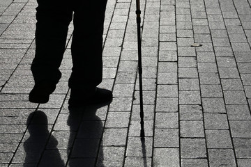 Silhouette of limping man walking with a cane, long shadow on pavement. Concept for disability, old age, blind person, dramatic life