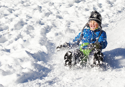 Cute young boy sprayed with snow as he is sledging down a hill